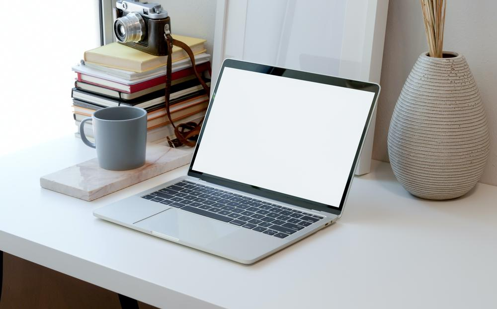 Canva_-_Laptop_and_cup_of_hot_drink_on_white_table.jpg